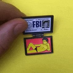 "Mulders wallet from X Files x The Simpsons Season cross over episode  ( 8 episode 10 - The Springfield Files )  • 1.25"" • Secure black rubber clasp • Comes on a heavy weight linen finished backing card • Ships as a single pin on a backing card"