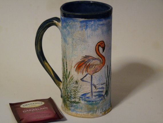 You can almost feel the warm sands and tropical heat with this Pink Flamingo Mug. There are two pink feathered birds to delight your senses, one on each side of the mug,. You will get much pleasure when using it to sip your steaming cup of coffee or tea. This is a OOAK (one of a kind) mug and was made using a slab of clay, then hand formed, two flamingos and leaves pressed in, and a handle added. It was not thrown on the potters wheel. It was hand painted using lead free glazes. The inside…