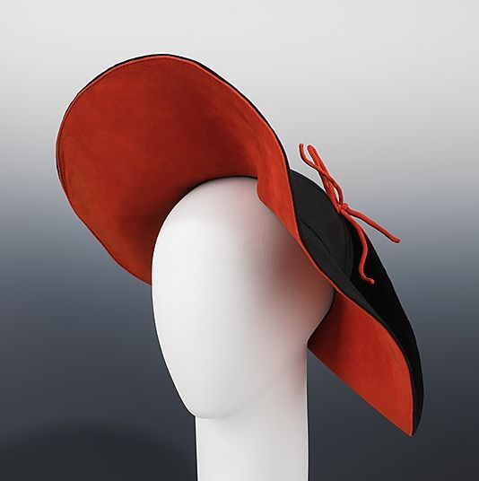 Black and orange wool and leather hat (front), by Sally Victor, American, 1939. In dramatic orange and black, this hat gives the illusion that the brim is being pulled over the crown at back, a modern, almost surreal, element. Victor was known for her artistic sensibility, and this asymmetric unconventional design attests to that idiosyncrasy. The softly textured materials, fur felt and suede, would be perfectly suited for a winter or fall ensemble.