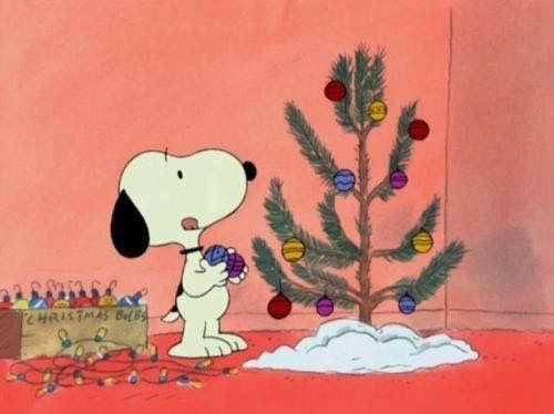 Snoopy decorating a Christmas tree