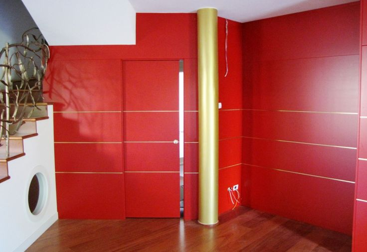Boiserie moderna rossa realizzata a completamento di un salone boiserie rossa già pubblicato per l'ingresso della casa. La boiserie ha distanziatori in filo di ottone . Possiamo realizzare qualsiasi tipologia di boiserie moderne in falegnameria sempre con laccature personalizzate a campione e pannelli boiserie  di dimensione e forma su disegno