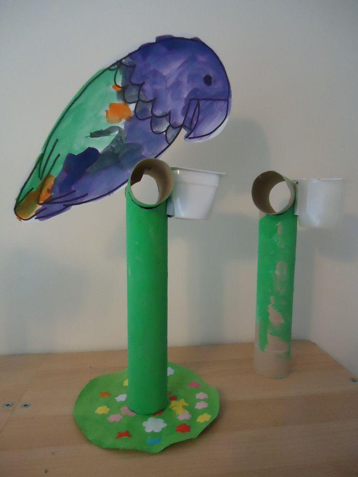 Papegaai op stok. Papegaai aan twee kanten laten verven/kleuren. De stok is gemaakt van 1 keukenrol en 1 wc rol. Het voederbakje is een bakje van een fruithapje.