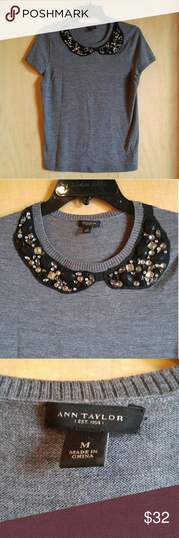 """Ann Taylor Gray Embellished Bib Wool Sweater Tee Ann Taylor top, size medium, in excellent condition save for two spots of discoloration shown in photo. May come out--I haven't tried to remove them. Asymmetrical black bib with silver stones and tie detail at back of neck. Thicker knit sweater material. Would look great tucked into a skirt! 18"""" pit to pit, 25"""" length. 100% extrafine merino wool. Please ask any questions. No trades. Make a reasonable offer. Thanks! Ann Taylor Tops Blouses"""