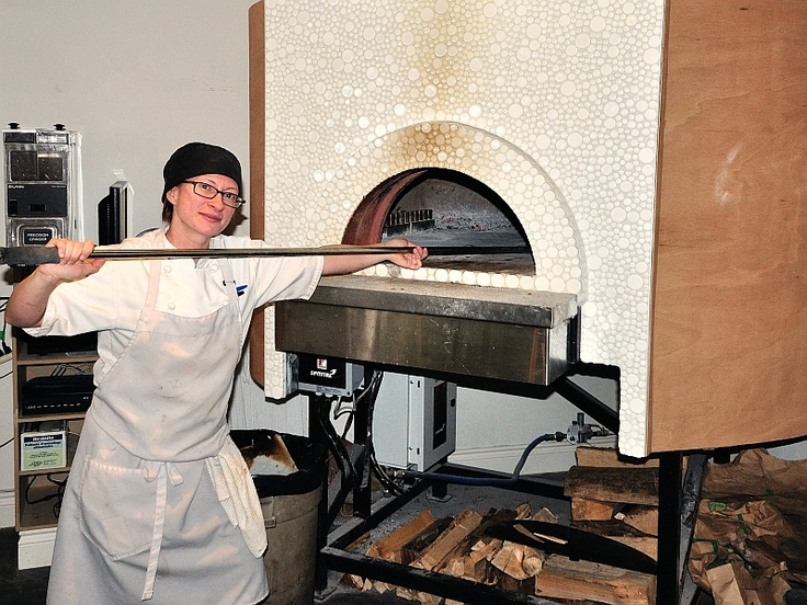 Boss Sarah Wallbank works the wood oven at Riso Restaurant & Bakery