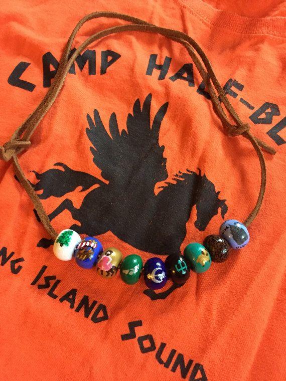 Avoir votre propre collier Camp Half Blood! Il se décline en deux styles: Annabeth Chase avec toutes les neuf perles ou Percy Jackson avec quatre billes (le trident, la Toison d'or, le labyrinthe et l'empire state building). S'il vous plaît gardez à l'esprit que j'ai à la main peinture tous ces et certaines couleurs ne correspondra pas exactement. Les perles sont faites en argile que je forme moi-même afin de leur donner un look unique. Puis chacune des billes sont peints puis enduit…