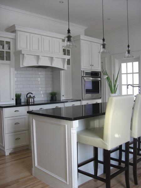 creamy white kitchen cabinets, subway tiles backsplash, black granite countertops, ivory leather stools, kitchen island and bell glass pendants.