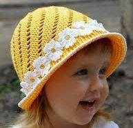 menina loira com chapeu de croche na cor amarela com faixa de rosas brancas