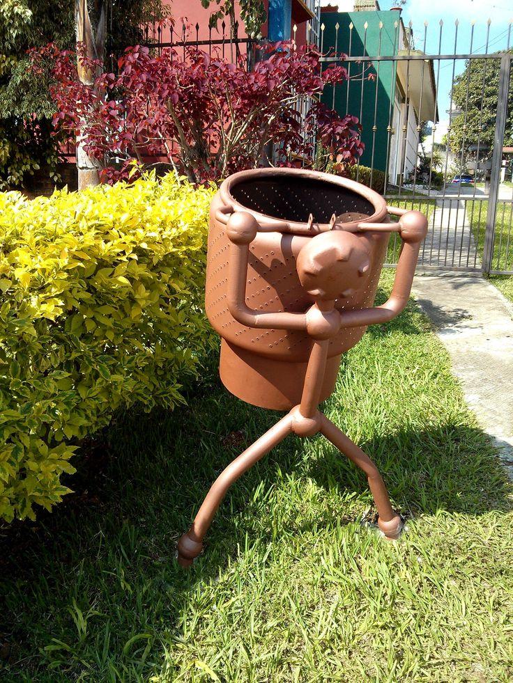 Bote de basura con material reciclado. El bote está hecho con una tina de lavadora. La cabeza se hizo con la base y la parte superior de un tanque de extintor y el cuerpo con tubo recuperado de la chatarra. Córdoba, México