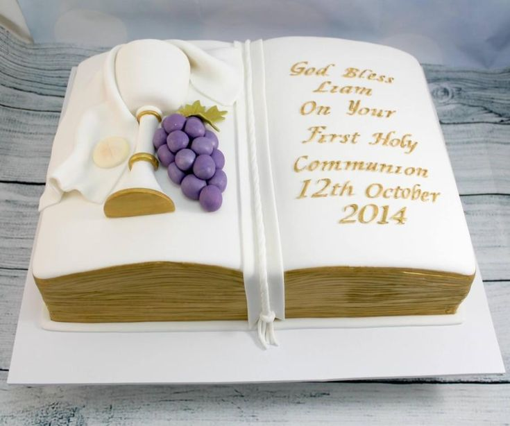 Holy communion cake in the shape of a bible, with hand made fully edible chalice,grapes, host and cloth. Edges , lettering and trim on chalice were hand painted with edible gold paint.