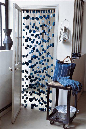 Rideau de porte formé de rubans de tissus bleus enroulés et accrochés à des fils de coton