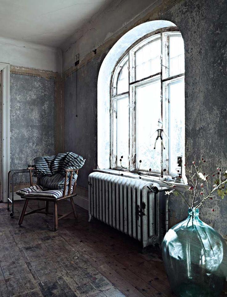 // En del möbler har stått kvar sedan husets första ägare bodde här. Nästan allt annat i hemmet är fyndat på loppisar i trakten. På golvet syns rester av tidningar daterade husets byggår, 1925. De användes som isolering mellan brädor och matta, men Christina tyckte att tidningsresterna var så dekorativa att hon klarlackat golvtiljorna.