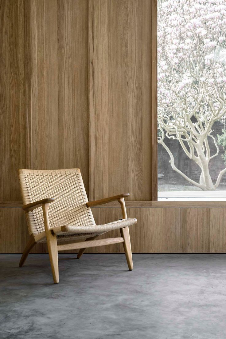 McLaren Excell adds pale-brick extension to black-painted Victorian house. Chair: CH25 by Hans J Wegner for Carl Hansen & Son