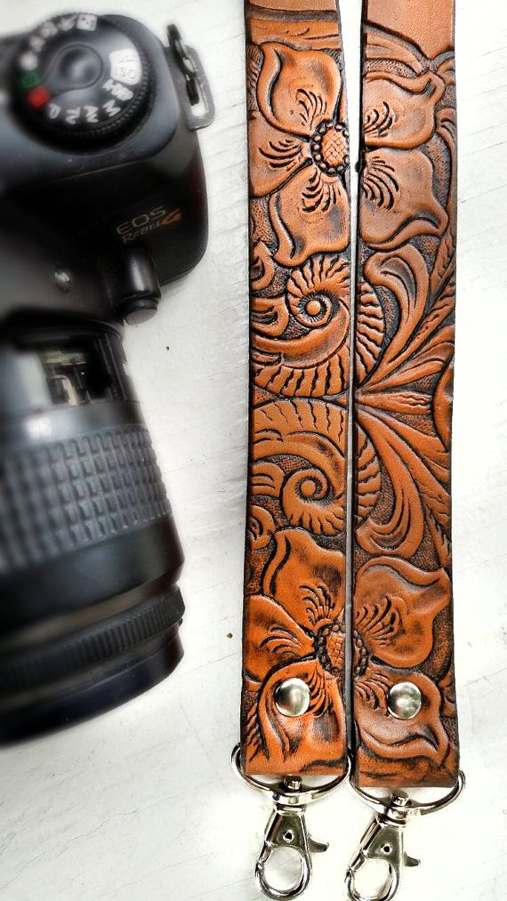 A textural western floral pattern adorns this custom, handmade camera strap - the flowers and vines cover each area above the clips and then frames