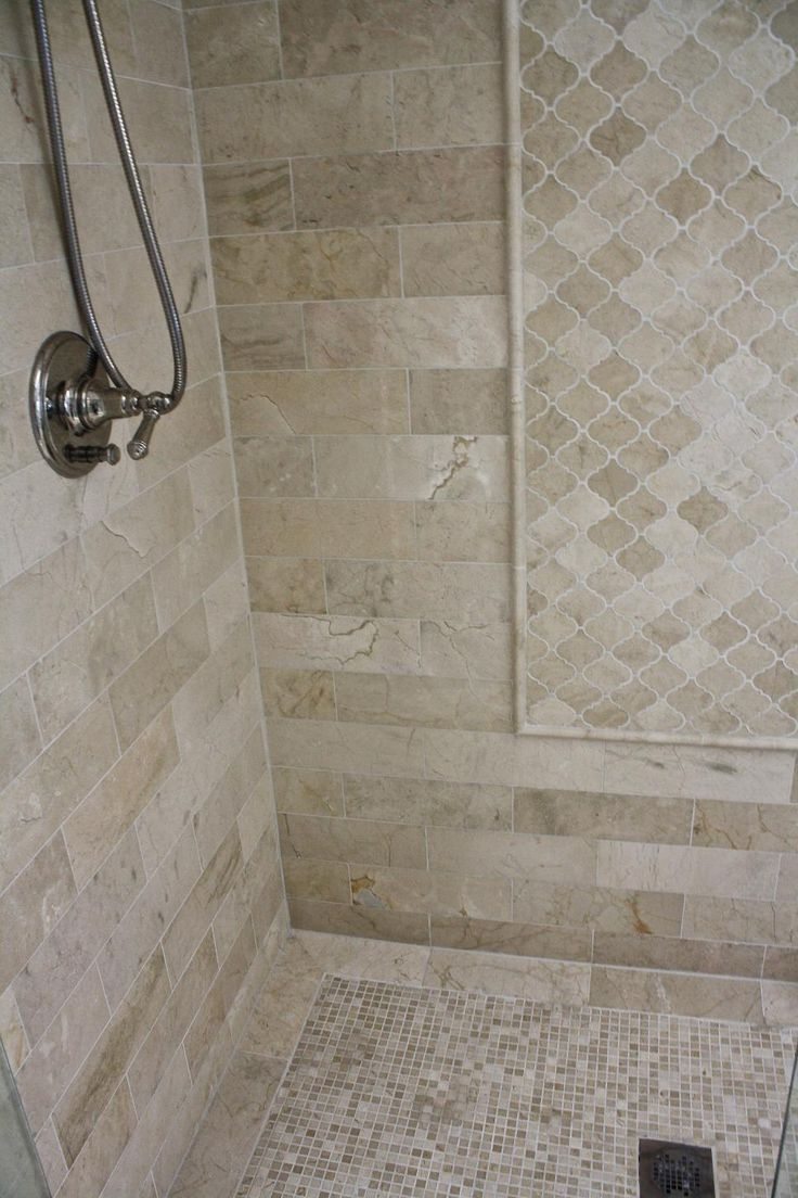 Different shaped tiles in the same color scheme and material bring dynamic visual interest into this shower.