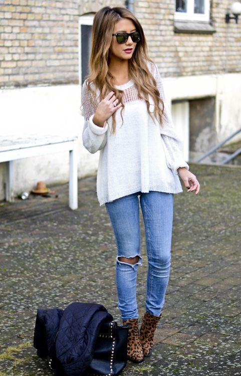 Loose sweater, ripped light wash jeans, and softly curled hair