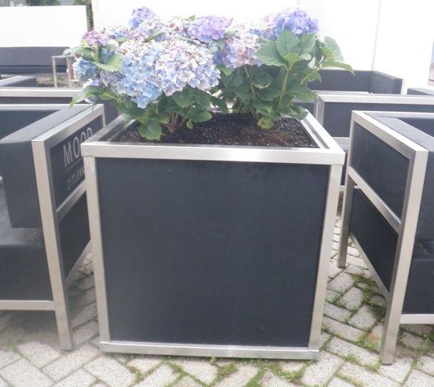Rvs plantenbak met zwart gestoffeerde zijpanelen, bijpassen bij de buitenmeubelen.