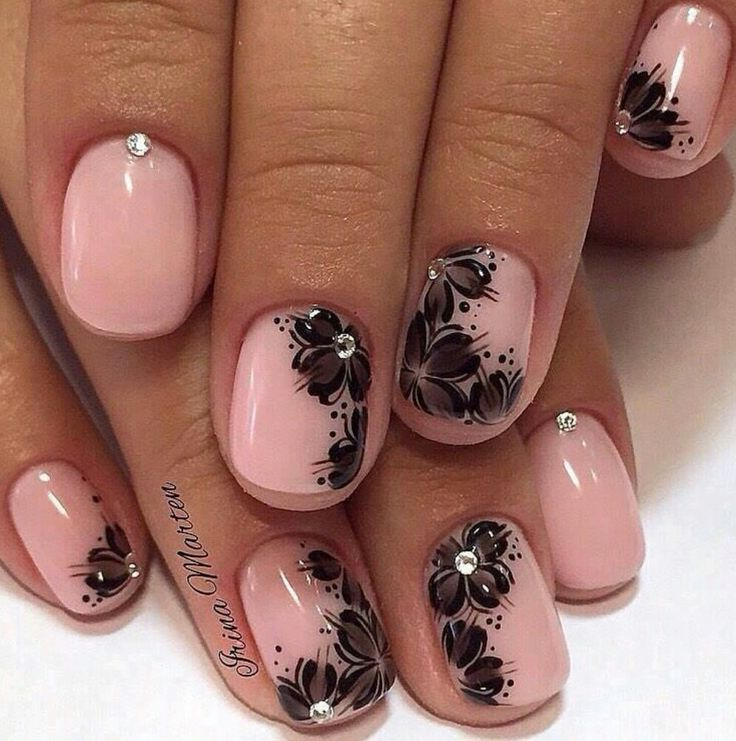 Pale pink nails with black hand painted flowers and crystals by Irina Marten