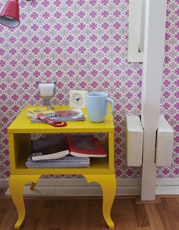 Yellow bedside table with books, mug and clock