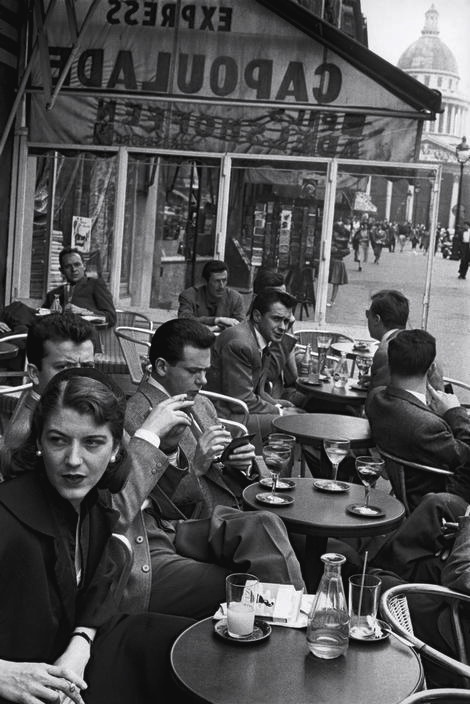 Paris 1954. I love the way cafes set up their tables outside. All the chairs face the street.