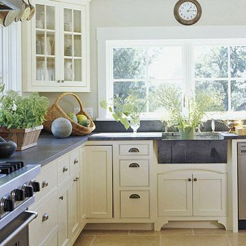 Gorgeous kitchen w/ cream cabinets, farmhouse sink, stone countertops, and a giant window