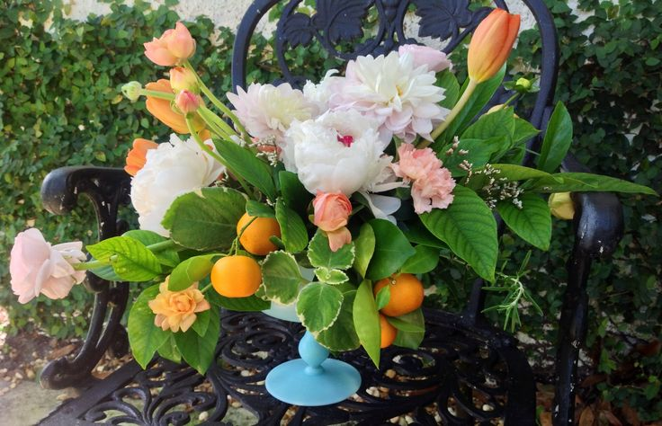 Citrus and flower arrangement in vintage blue glass container features orange tulips, pink and peach ranunculus , white peonies, peach dahlia, oregano, carnations, fresh kumquat branches and fruit.