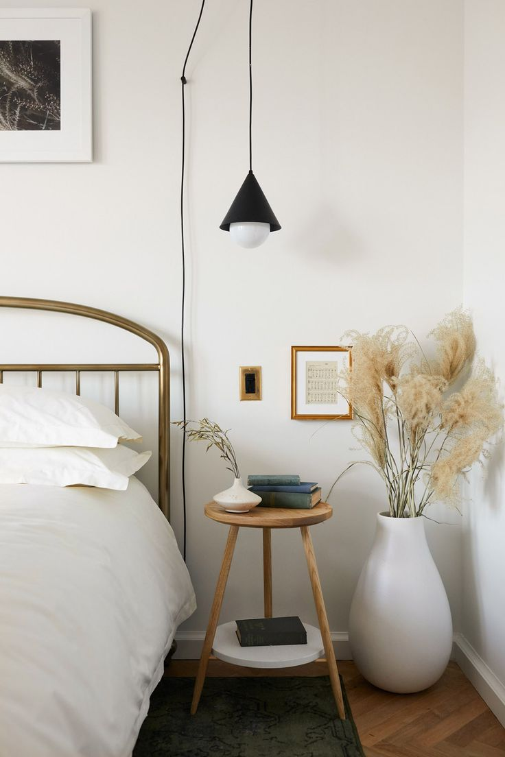 A cozy and minimal bedroom with a vase filled with pampas grass for texture