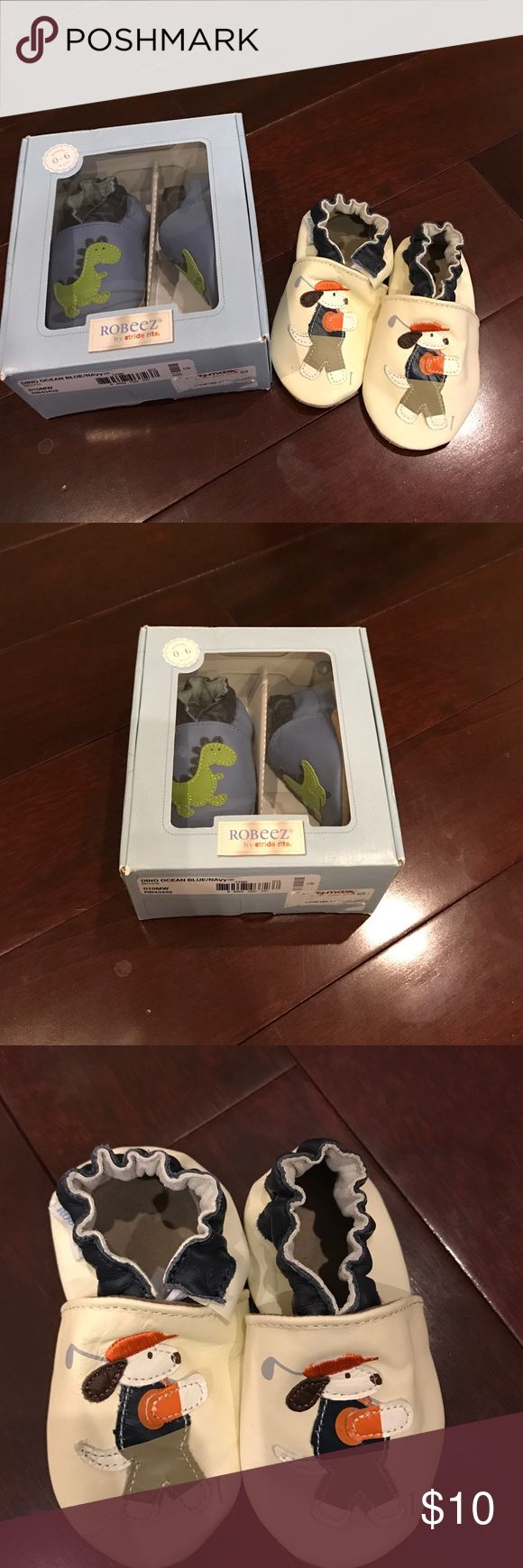 Robert Crib shoes by Stride Rite. Two pairs Two pairs of Robeez Crib shoes.Dino Ocean navy blue are brand new in box never worn size 0-6 months. Golfing puppy is 6-12 months also never been worn but no box. Excellent condition. Robeez Shoes Baby & Walker