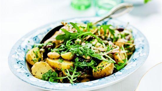 Koka potatisen med skal i saltat vatten. Låt den kallna något. Blanda senap och vinäger i en stor skål. Vispa droppvis in oljan till en krämig dressing. Halvera potatisen och vänd ned senapsdressingen i potatisen. Låt svalna. Blanda den krämiga potatisen med skivad lök, kapris, bönor, oliver och rucola. Smaka av med salt, peppar och lite olivolja