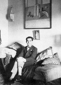 """Federico García Lorca sentado en su casa de Granada en 1925, bajo el óleo """"Naturaleza muerta"""" regalado por Salvador Dalí."""