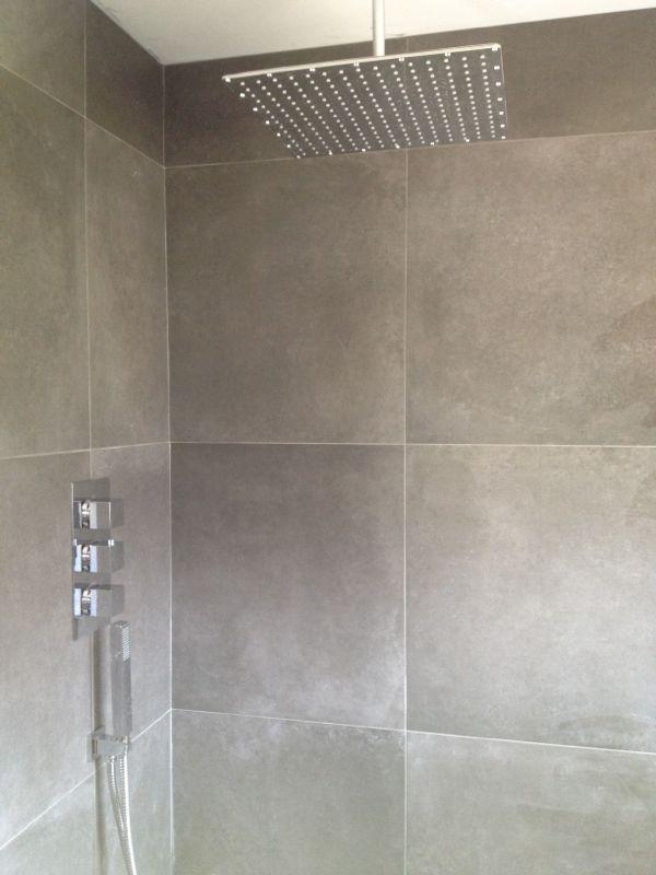 Bathroom, grey large tiles. Large shower head.