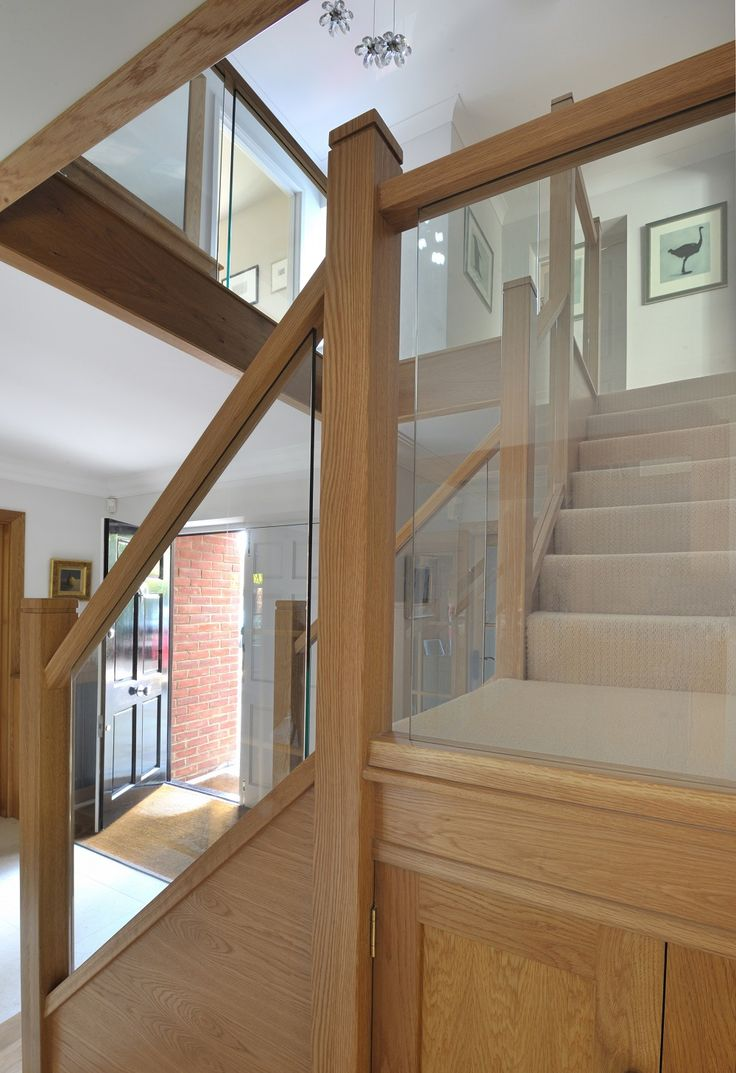 A centrally positioned oak and glass staircase with a half landing turn and gallery landing for Home designer stairs with landing