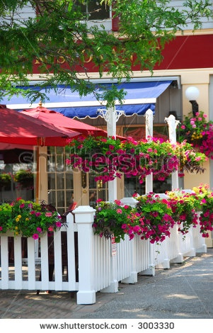 stock photo : Pretty restaurant patio decorated with purple petunia flower boxes and baskets
