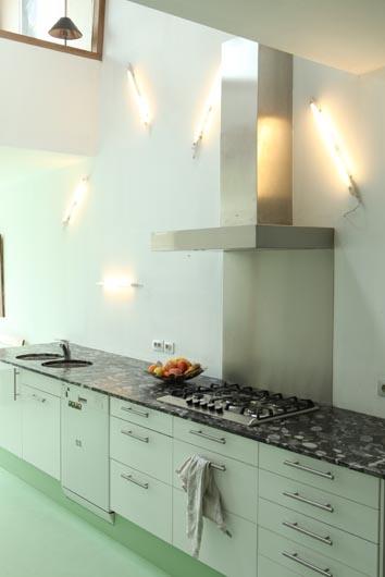 Gedurfd: muntkleurige keuken (en vloer) met zwart marmeren werkblad
