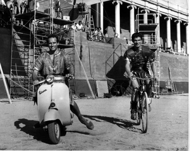 Charlton Heston and Stephen Boyd on the set of BEN-HUR horsing around with a Vespa