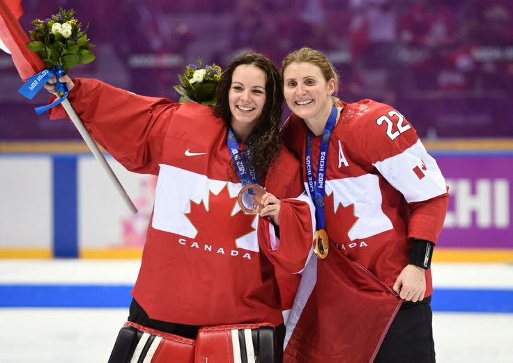 Hayley Wickenheiser and goalie Shannon Szabados hold their gold medals for photographers following the medal ceremony in Sochi, Russia, Friday, February 21, 2014. (Paul Chiasson / THE CANADIAN PRESS)