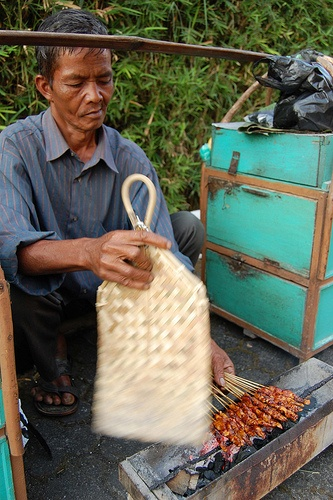 mm..Sate...A man preparing Chicken Satay to eat