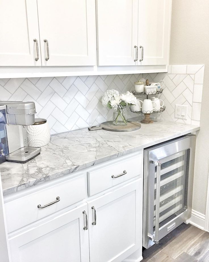 small butlers pantry with herringbone backsplash tile and white quartzite countertop away from the busy kitchen nearer to the couch