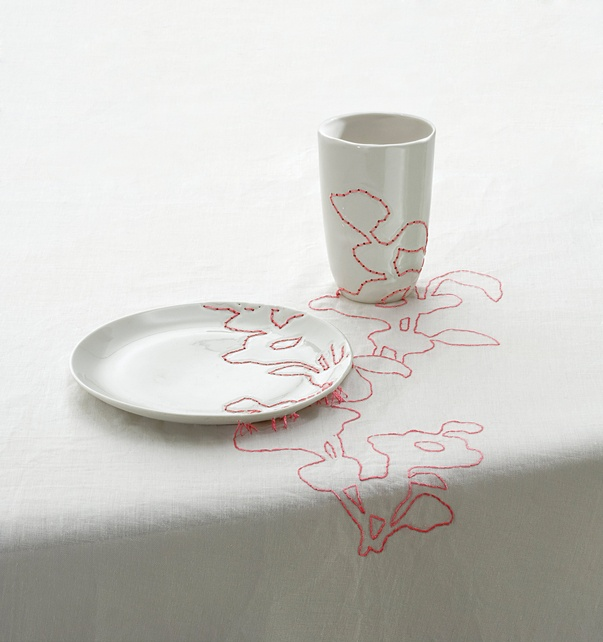Embroidered tablecloth continues patterns derived from Ming vases across plates and cups.