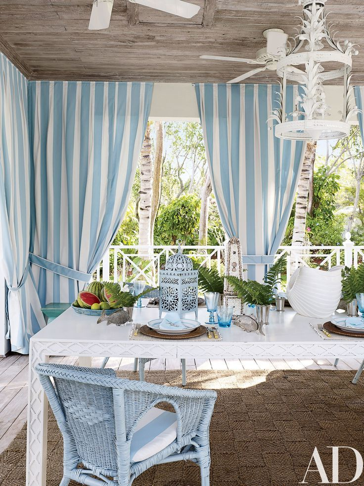 Miles Redd Turns a Bahamas Residence Into a Showstopping Beach Home Photos | Architectural Digest: A dining pavilion, which overlooks the pool, is lined with curtains made of an awning-stripe Perennials fabric.