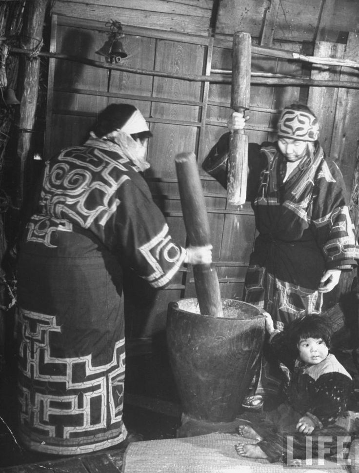 Ainu village women pounding rice in hollowed-out stump with wooden clubs, Shiraoi, 1946 by Alfred Eisenstaedt