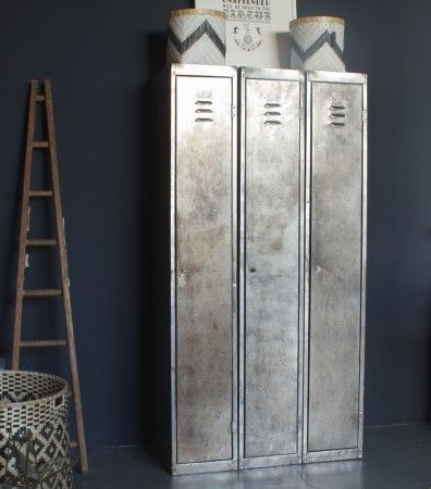 Contrast- glossy metallic silver locker storage contrasts the matte navy blue/grey of the wall