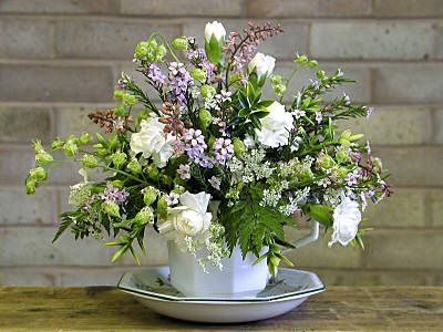 A dainty flower arrangement is a cup and saucer with white flowers and greenery