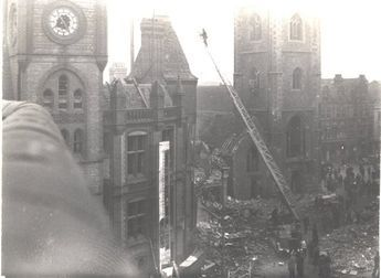 On 10 February 1943, four bombs were dropped on Reading town centre. The Town Hall on Blagrave Street was badly damaged as were businesses on Minster Street. 41 people were killed, mostly customers at the People's Pantry in Market Arcade. This photograph showing a fire engine by the Town Hall and St Laurence's Church was taken in the aftermath of the bombing from the parapet of Somerset House, Friar Street.