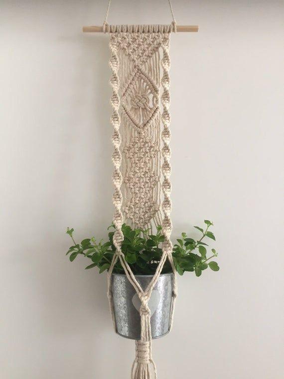 Deze plantenhanger is handgemaakt van mooie ivoor witte of lichtgrijze katoentouw (4 mm) en hangt aan een blank houten stok. AFMETINGEN Totale lengte: 73 cm/29 inch (gemeten excl. het ophangkoord). De breedte van de houten stok is 20 cm/8 in. Potmaat: 9-12 cm/3.5-4.5 inch. De pot en de plant zijn