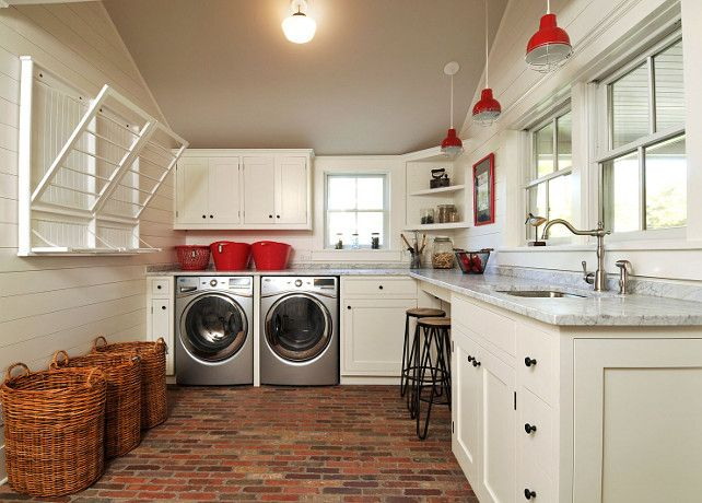 This laundry room is just perfect! I love the cabinet layout, the wall-mounted pull down laundry rack and the laundry folding station. The red decor compliments the brick flooring.