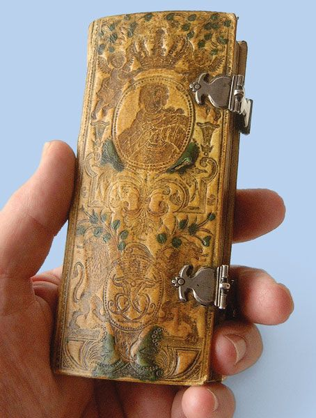 Psalm Book: Small size is typical of Scandinavian Lutheran texts. The colored bookbinding, however, is quite unusual. The binding probably dates from the rule of King Frederic V of Denmark, between 1746 & 1766. The tooling depicts 2 cherubs crowning Frederic at the top, with rampant lions & the king's monogram below. The small silver clasps are delicate & finely wrought. Typical of the era, the silversmith did not use a hallmark, & the artist's identity is not known.
