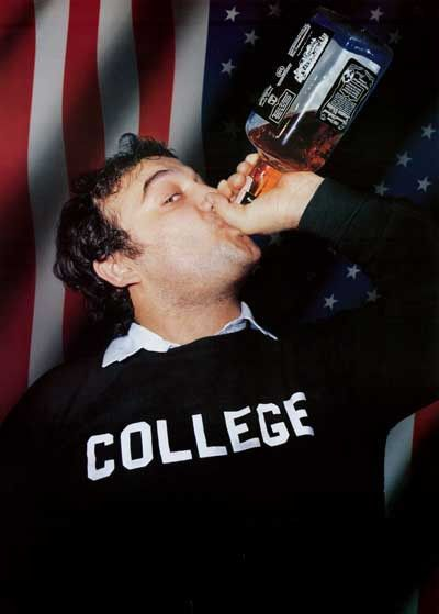 "Picture of Jim Belushi from the movie ""Animal House,"" wearing a shirt that says, ""COLLEGE"" and chugging a bottle of Jack Daniels whiskey"