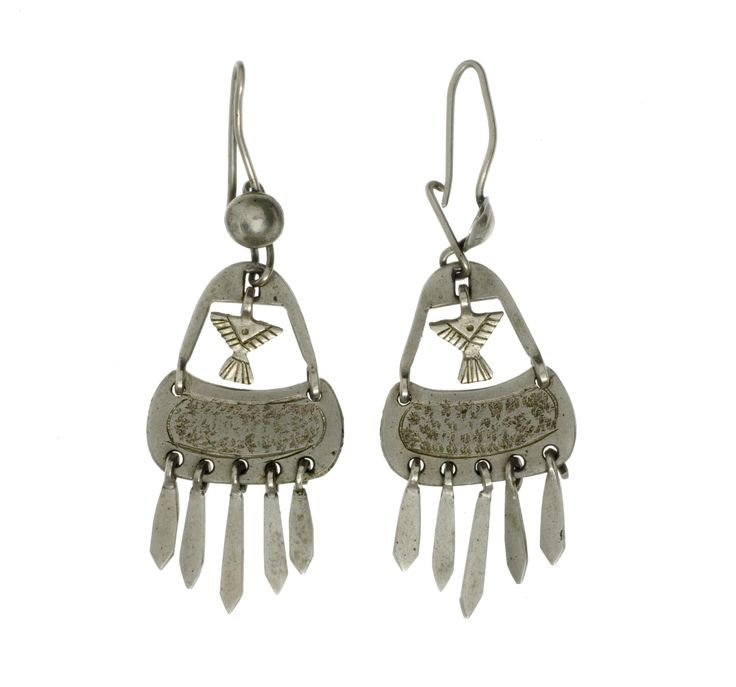 Earring, one of a pair, of silver, consisting of a hook with boss from which hangs an open, hinged triangular body perforated at lower edge to take five graded pendants, with small pendant in form of a stylised bird hanging within the triangular opening: Americas, USA, Oklahoma, Kiowa, mid 20th century