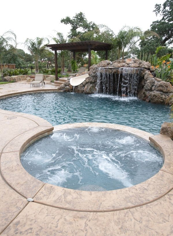 this gunite swimming pool has an inset hot tub with a rock waterfall and slide