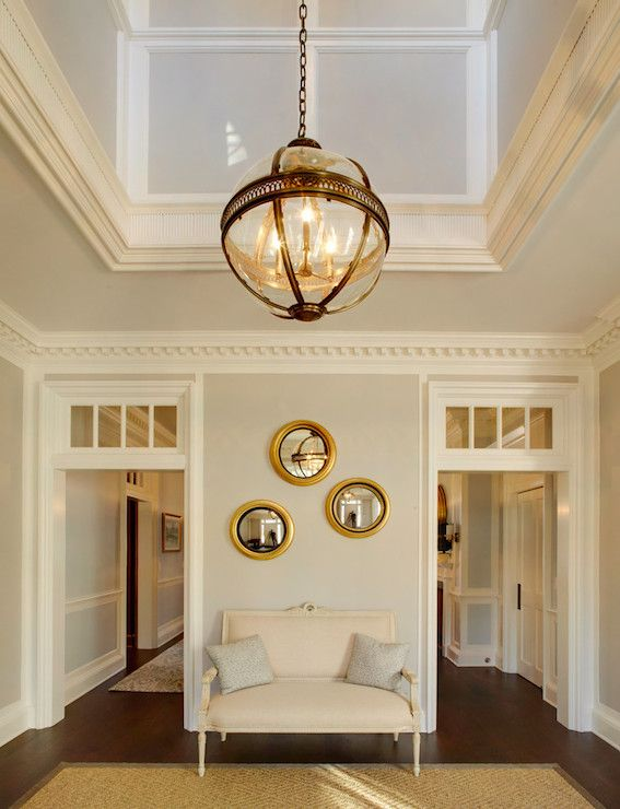 Incredible two story foyer illuminated by a Restoration Hardware Victorian Hotel Pendant over gray walls finished with dentil crown molding above doorways with transom windows.